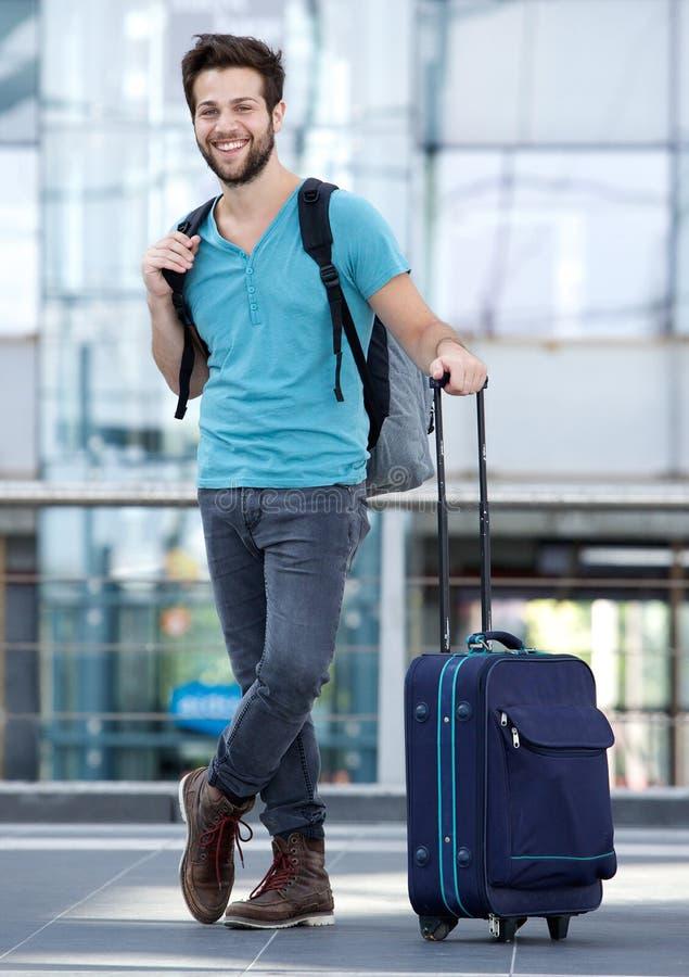 Homem novo que espera no aeroporto com mala de viagem e saco imagem de stock royalty free