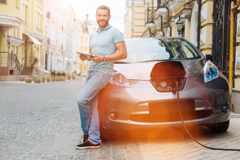 Homem novo que espera seu carro a ser carregado fotografia de stock royalty free
