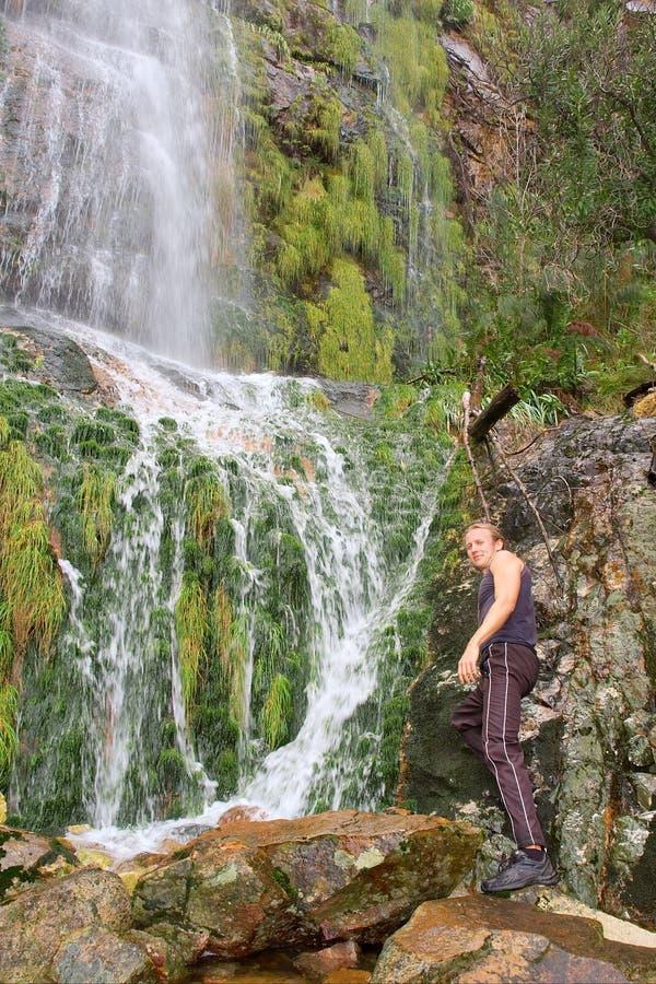Homem novo que está ao lado da cachoeira imagem de stock royalty free
