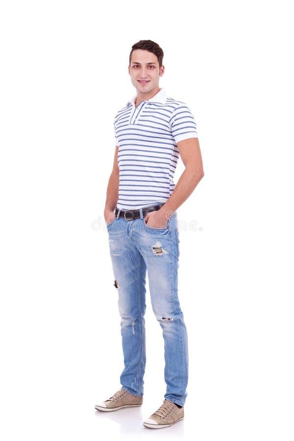 Homem novo que está com mãos em uns bolsos foto de stock
