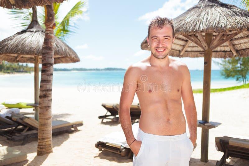 Homem novo que está com mãos em uns bolsos na praia foto de stock royalty free