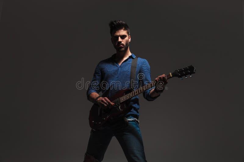 Homem novo que está e que joga a guitarra elétrica foto de stock