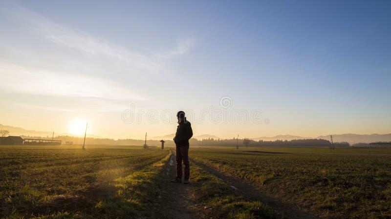 Homem novo que está na estrada secundária em um olhar bonito da paisagem imagem de stock royalty free