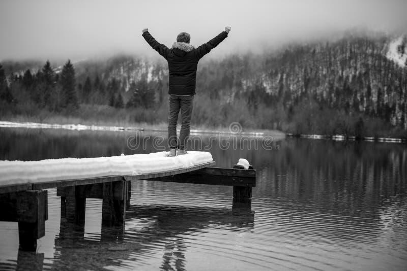 Homem novo que está na extremidade do cais de madeira em um lago imagens de stock
