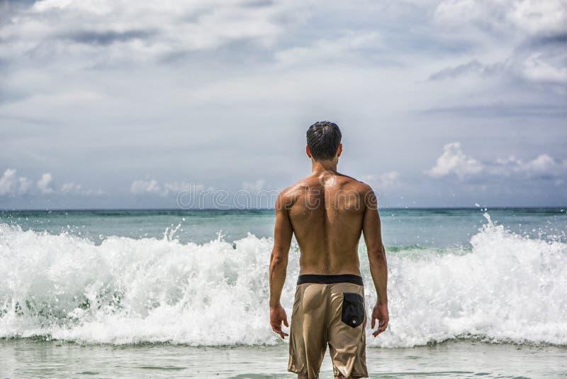 Homem novo que está na praia pelo oceano imagens de stock royalty free