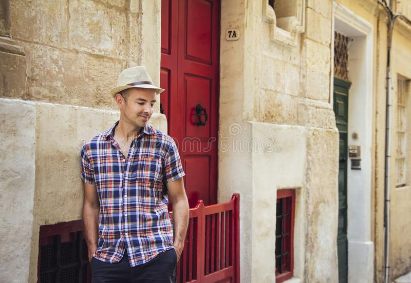 Homem novo que está na rua velha em Malta imagem de stock