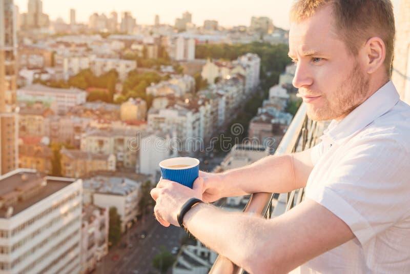 Homem novo que está no balcão alto da construção da elevação com o copo de papel com bebida quente, vista inspirador de negligênc fotografia de stock royalty free