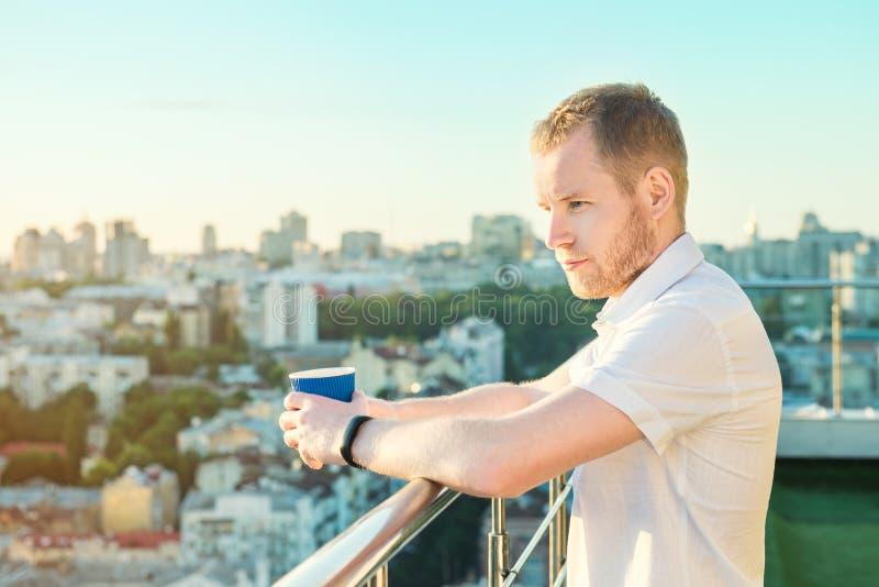 Homem novo que está no balcão alto da construção da elevação com o copo de papel com bebida quente, vista inspirador de negligênc fotografia de stock