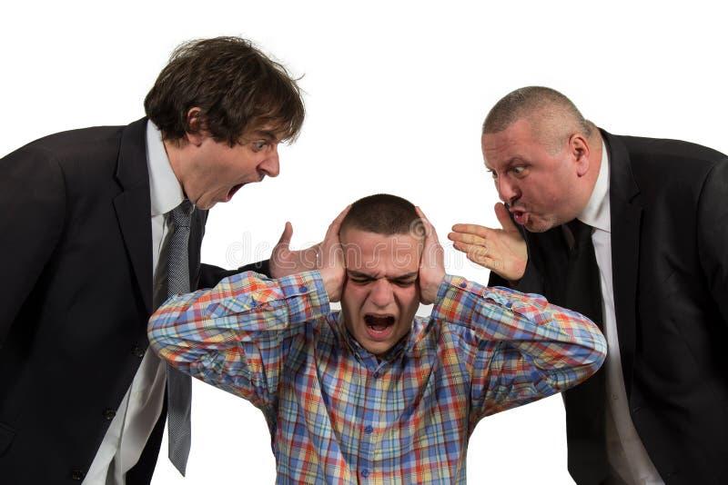 Homem novo que está sendo gritado no gerente masculino de perto dois sêniores no branco fotos de stock royalty free