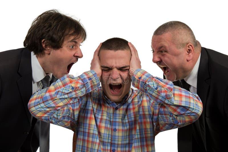Homem novo que está sendo gritado no gerente masculino de perto dois sêniores no branco imagens de stock royalty free