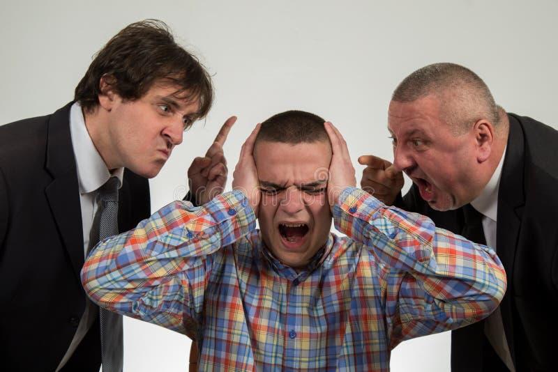 Homem novo que está sendo gritado no gerente masculino de perto dois sêniores no branco fotos de stock
