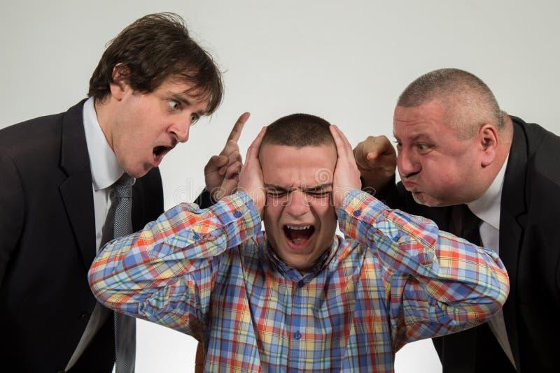 Homem novo que está sendo gritado no gerente masculino de perto dois sêniores no branco fotografia de stock royalty free