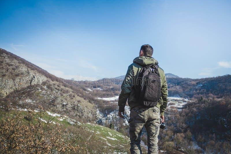 Homem novo que está sobre o penhasco nas montanhas do inverno que guardam a imagem de stock royalty free