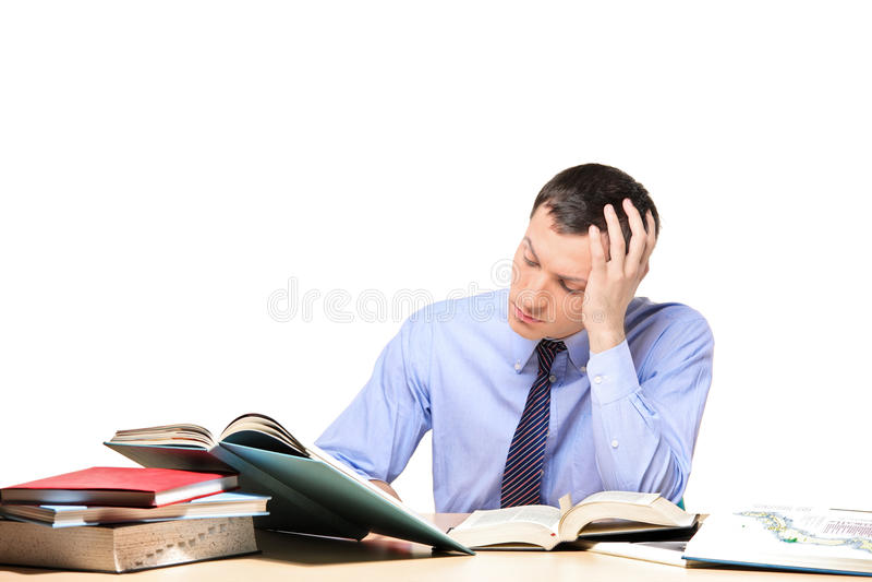 Homem novo que estuda algum problema assentado em uma tabela imagem de stock royalty free
