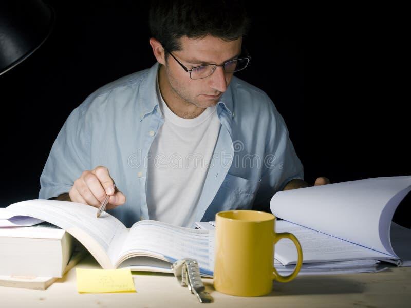 Homem novo que estuda na noite imagens de stock royalty free