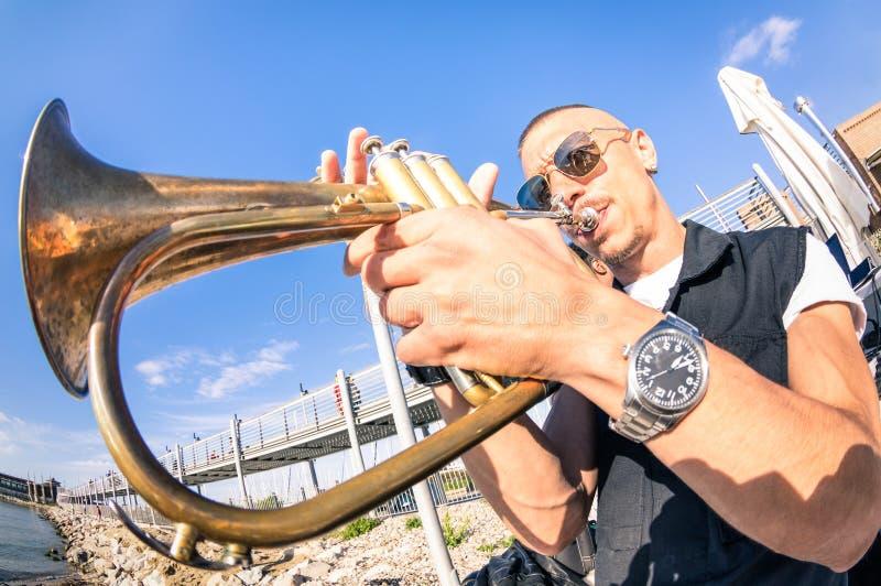 Homem novo que executa o jazz de solo da trombeta no partido da praia fotos de stock royalty free