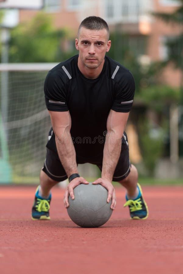 Homem novo que exercita Impulso-UPS na bola de medicina exterior fotografia de stock royalty free
