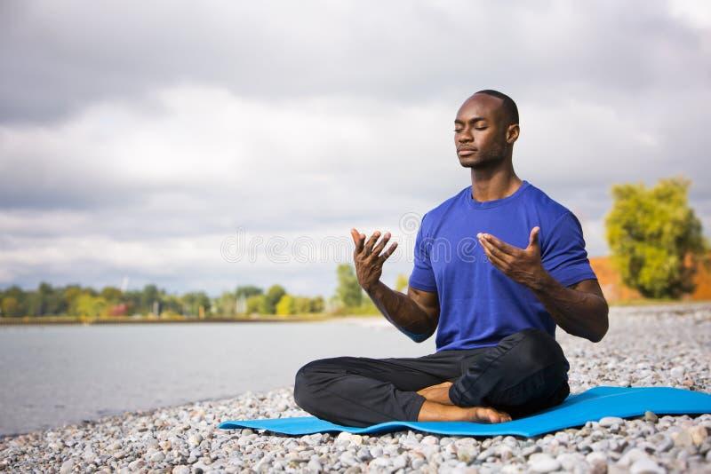 Homem novo que exercita a ioga imagem de stock