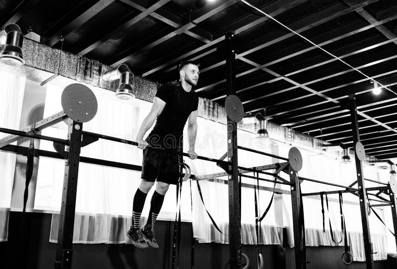 Homem novo que exercita na barra horizontal no gym Tríceps e bíceps dando certo adultos masculinos na barra horizontal como o tre imagem de stock