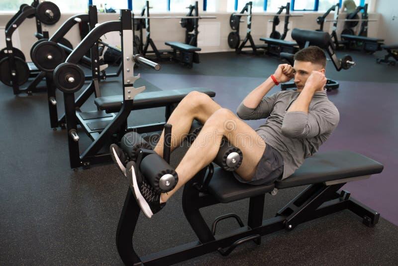 Homem novo que exercita na ginástica imagens de stock