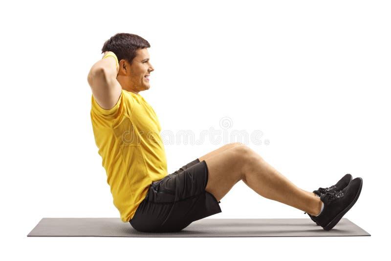 Homem novo que exercita o Abs no assoalho foto de stock