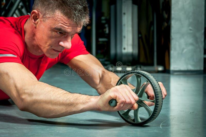 Homem novo que exercita o exercício da aptidão para abdominal com tonificação da roda imagem de stock royalty free