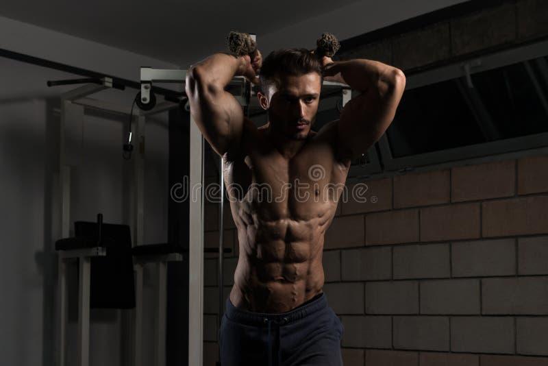 Homem novo que exercita o tríceps no Gym imagem de stock