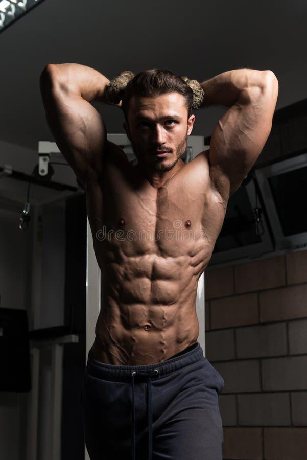Homem novo que exercita o tríceps no Gym imagem de stock royalty free