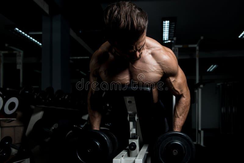 Homem novo que exercita para trás no Gym imagens de stock