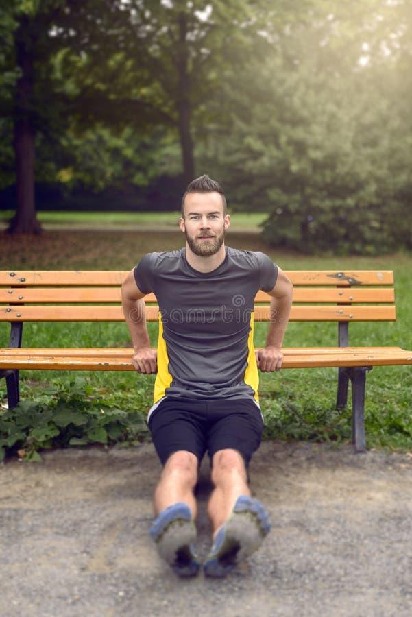 Homem novo que exercita usando um banco de parque de madeira fotos de stock royalty free
