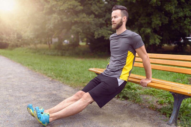 Homem novo que exercita usando um banco de parque de madeira fotografia de stock royalty free