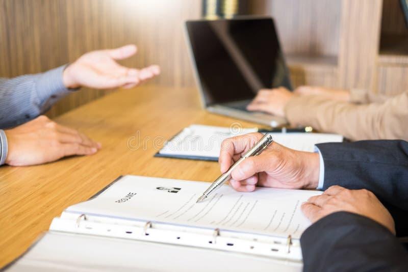 Homem novo que explica sobre seu perfil aos diretores empresariais que sentam-se na entrevista de trabalho escute as respostas do fotografia de stock
