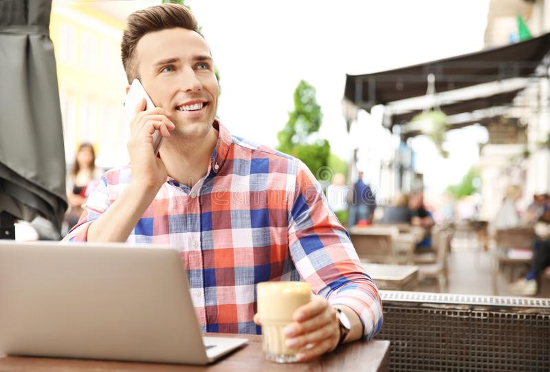 Homem novo que fala no telefone ao trabalhar com portátil fotografia de stock royalty free