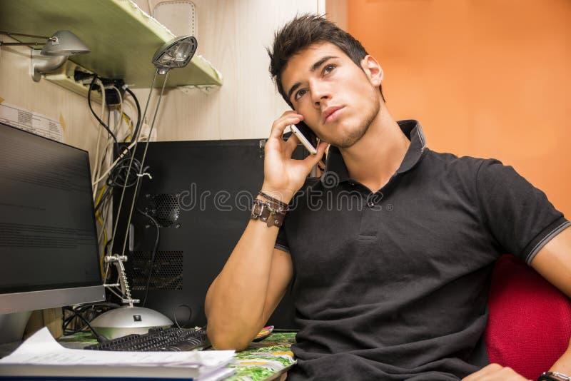 Homem novo que fala no telefone celular na mesa do computador imagem de stock royalty free
