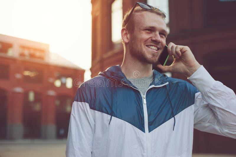 Homem novo que fala no telefone celular na rua foto de stock