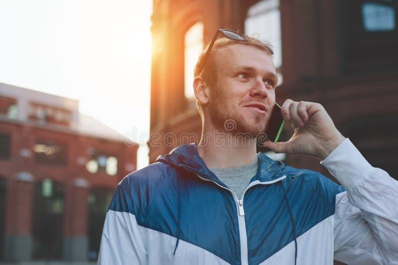 Homem novo que fala no telefone celular na rua no por do sol imagem de stock royalty free
