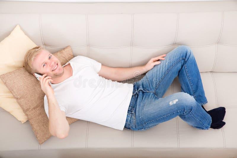 Homem novo que fala no telefone em casa foto de stock royalty free