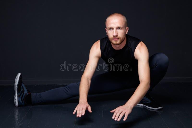 Homem novo que faz esticando o exercício foto de stock royalty free