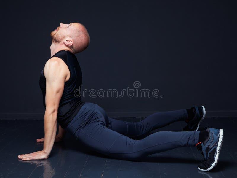 Homem novo que faz esticando o exercício fotografia de stock royalty free