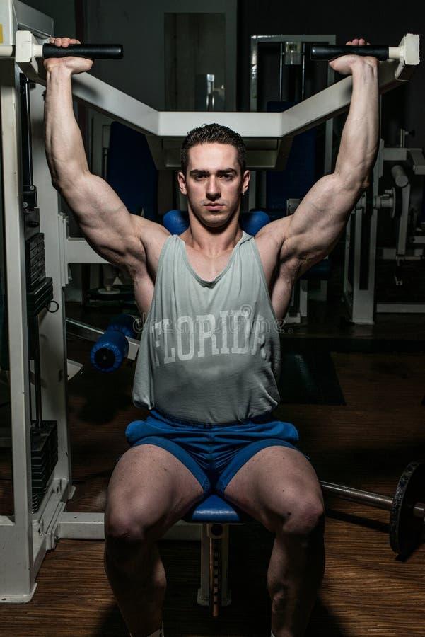 Homem novo que faz a imprensa do ombro na máquina no gym fotografia de stock royalty free