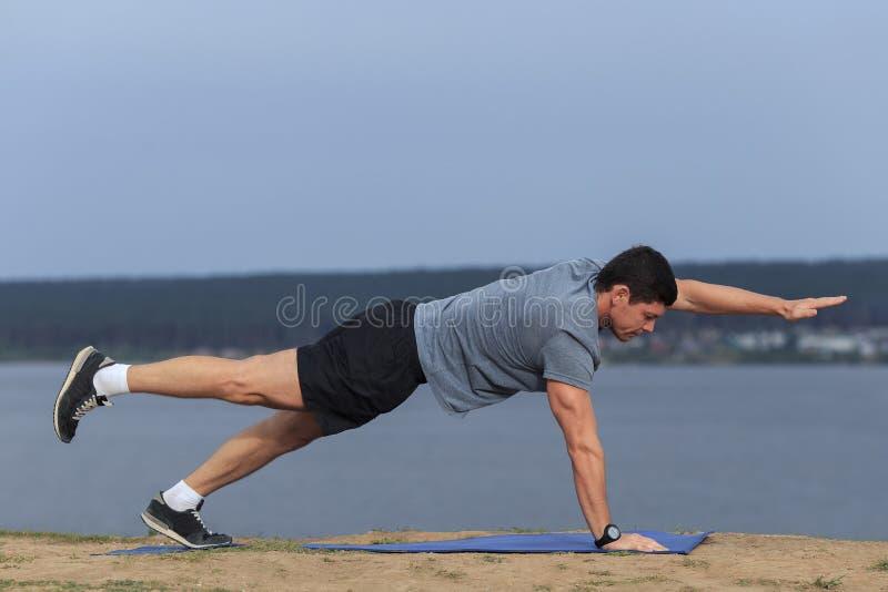 Homem novo que faz a ioga fora no ambiente natural fotografia de stock royalty free