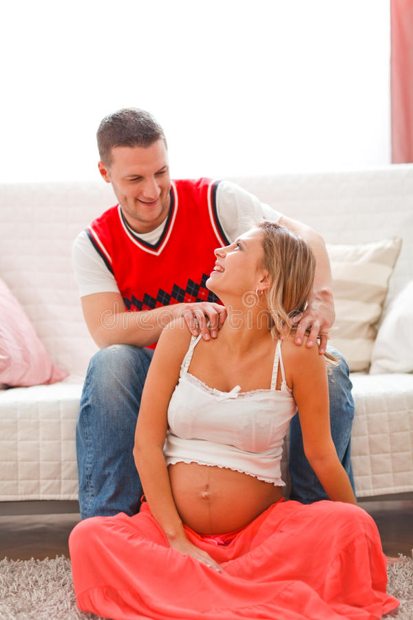 Homem novo que faz a massagem sua esposa grávida imagens de stock
