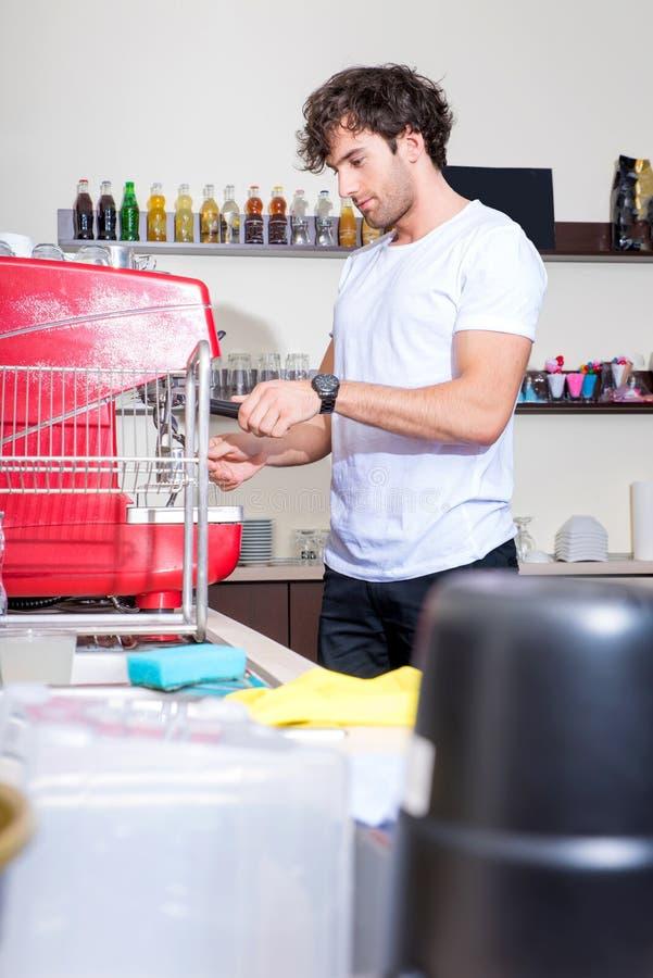 Homem novo que faz o café imagens de stock