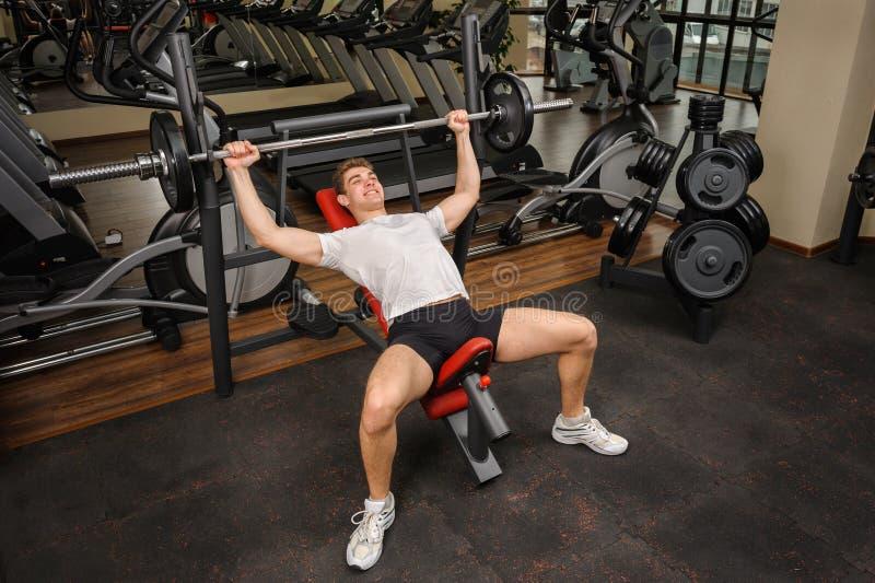 Homem novo que faz o exercício da imprensa de banco do declive do Barbell no gym foto de stock royalty free