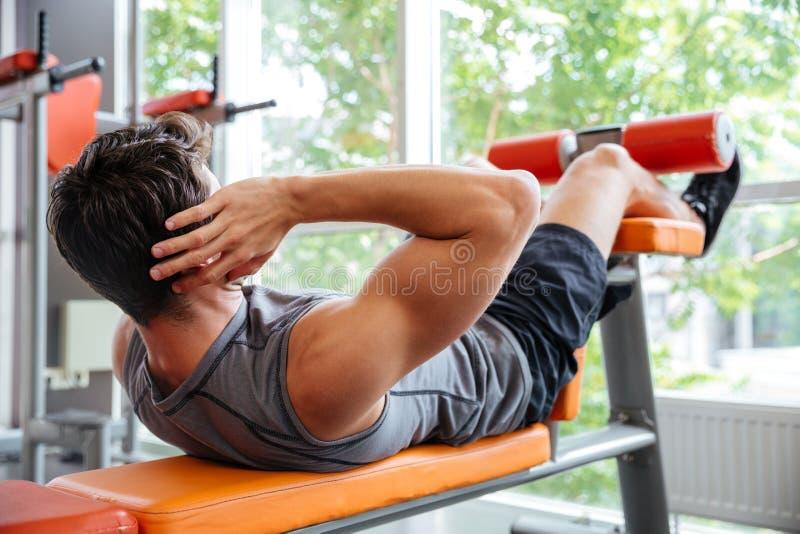 Homem novo que faz o exercício da imprensa de banco no gym fotografia de stock