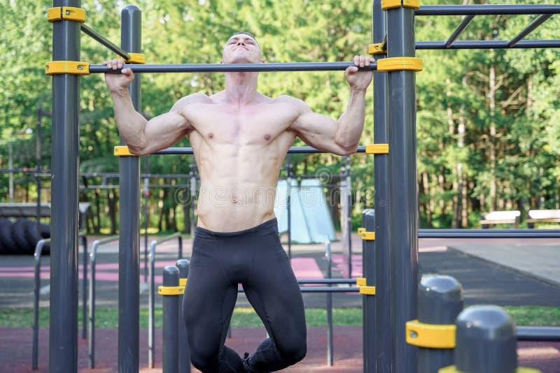 Homem novo que faz o exercício em uma barra horizontal fora fotografia de stock