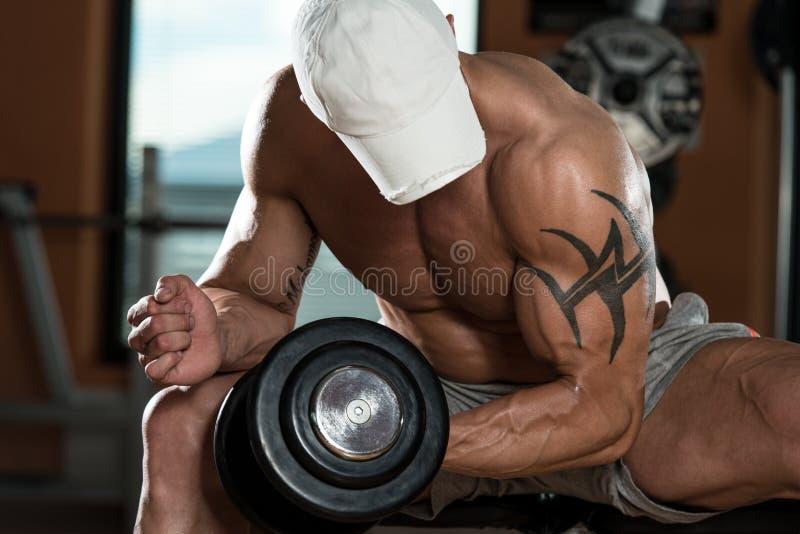 Homem novo que faz o exercício para o bíceps fotos de stock royalty free