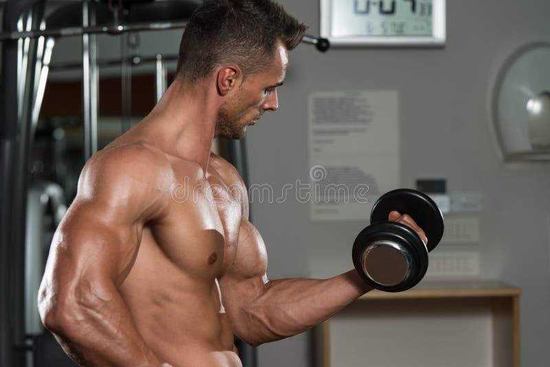 Homem novo que faz o exercício para o bíceps fotos de stock