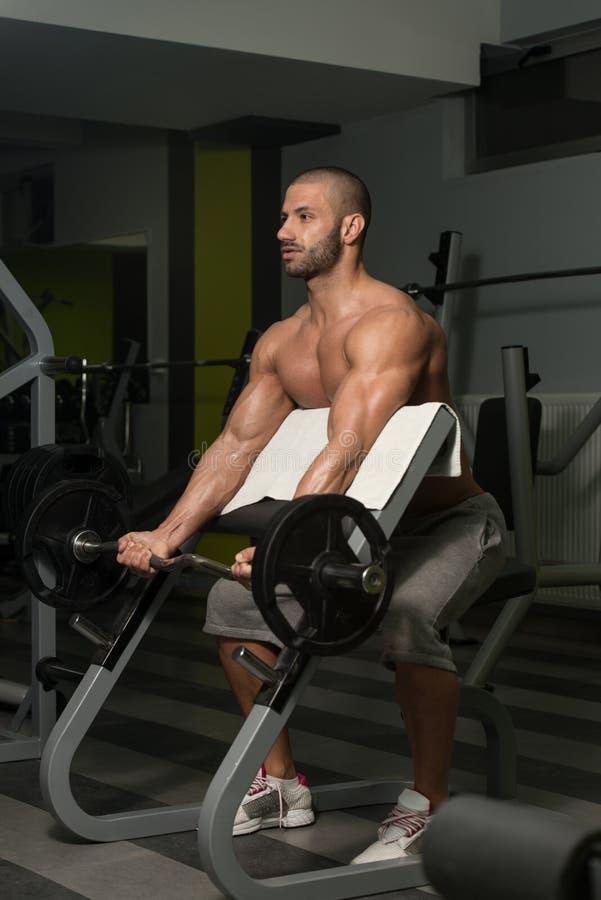 Homem novo que faz o exercício para o bíceps imagem de stock royalty free
