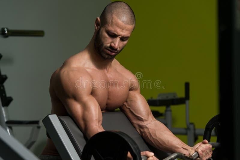 Homem novo que faz o exercício para o bíceps imagens de stock